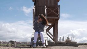 La mujer de moda se sienta por la torre y las miradas del rescate en el mar almacen de video