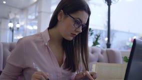 La mujer de negocios acertada en vidrios trabaja con el ordenador portátil y toma notas en ideas del negocio del planeamiento del almacen de video