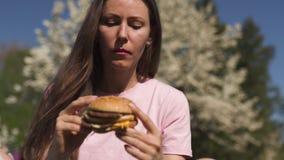 La mujer de negocios acertada que come el cheesburger de la hamburguesa de los alimentos de preparación rápida disfruta de su tie almacen de metraje de vídeo