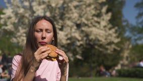 La mujer de negocios acertada que come el cheesburger de la hamburguesa de los alimentos de preparaci?n r?pida disfruta de su tie metrajes