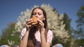 La mujer de negocios acertada que come el cheesburger de la hamburguesa de los alimentos de preparaci?n r?pida disfruta de su tie almacen de video