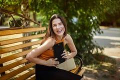 La mujer de negocios alegre y feliz con una tableta se sienta en un banco con un bolso Artilugio a disposici?n foto de archivo libre de regalías