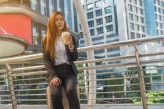 La mujer de negocios asiática bebe el café en bolso de la maleta fotografía de archivo