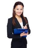 La mujer de negocios asiática escribe en el tablero Fotos de archivo