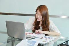 La mujer de negocios asiática está utilizando el ordenador portátil en una oficina foto de archivo