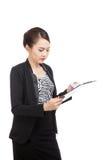 La mujer de negocios asiática joven leyó el papel en el tablero Fotografía de archivo