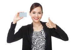 La mujer de negocios asiática joven manosea con los dedos para arriba con una tarjeta en blanco Imágenes de archivo libres de regalías
