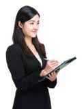 La mujer de negocios asiática toma la nota sobre el tablero Imagenes de archivo