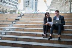 La mujer de negocios asiática y el hombre de negocios caucásico se sientan en la escalera y sostienen un papel del informe financ Fotografía de archivo
