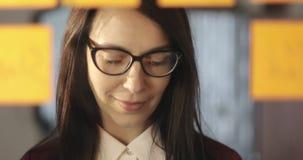 La mujer de negocios atractiva en vidrios escribe la información en etiquetas engomadas y la pega en el vidrio en la oficina almacen de video