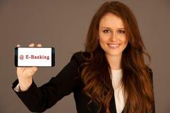 la mujer de negocios atractiva lleva a cabo e-actividades bancarias del smartphone Foto de archivo libre de regalías
