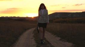 La mujer de negocios atractiva que camina a lo largo de una carretera nacional con una cartera a disposici?n, el sol riela en la  almacen de metraje de vídeo