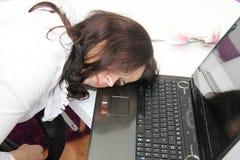 La mujer de negocios cansada se cayó dormido al lado de un ordenador portátil Fotos de archivo libres de regalías