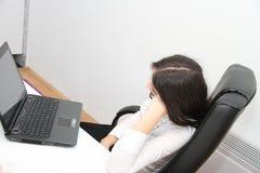La mujer de negocios cansada se cayó dormido al lado de un ordenador portátil Foto de archivo