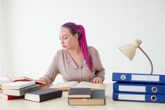 La mujer de negocios con el pelo rosado se sienta en la oficina lee la educación de los libros Foto de archivo