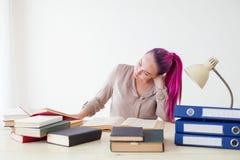 La mujer de negocios con el pelo rosado se sienta en la oficina lee la educación de los libros Foto de archivo libre de regalías