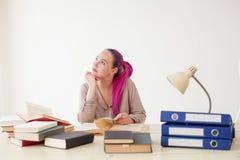 La mujer de negocios con el pelo rosado se sienta en la oficina lee la educación de los libros Fotos de archivo