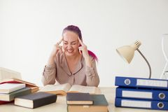 La mujer de negocios con el pelo rosado se sienta en la oficina lee la educación de los libros Fotografía de archivo libre de regalías