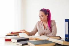 La mujer de negocios con el pelo rosado se sienta en la oficina lee la educación de los libros Imagenes de archivo