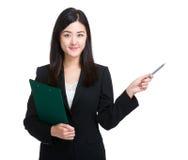 La mujer de negocios con el tablero y la pluma señalan Imagen de archivo libre de regalías