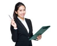 La mujer de negocios con el tablero y la pluma señalan Foto de archivo libre de regalías