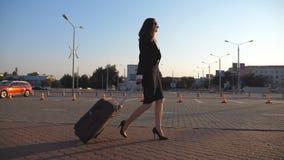 La mujer de negocios con la maleta camina al aeropuerto para ir en viaje de negocios Señora en zapatos de los tacones altos que c metrajes