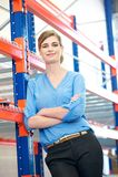 La mujer de negocios confiada que se relaja al lado de deja de lado los estantes en almacén Imagen de archivo libre de regalías