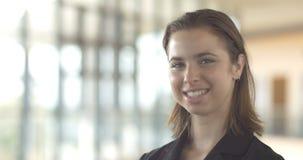 La mujer de negocios confiada sonriente hermosa que miraba la cámara aisló la oficina almacen de metraje de vídeo