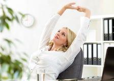 La mujer de negocios de mediana edad con los brazos sube la relajación imagen de archivo