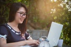 La mujer de negocios del primer utilizó el ordenador portátil para trabajar al aire libre, empañado imágenes de archivo libres de regalías