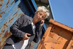 La mujer de negocios delante de los envases está llamando con el smartp foto de archivo libre de regalías