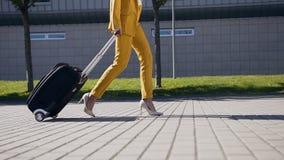 La mujer de negocios delgada en traje elegante tira de una maleta, se apresura a una reunión de negocios Mujer de negocios atract almacen de video