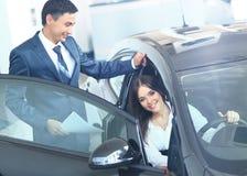 La mujer de negocios elige un coche en la oficina Fotografía de archivo