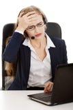 La mujer de negocios en el centro de atención telefónica está teniendo dolor de cabeza. Fotografía de archivo