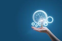 La mujer de negocios en la mano de un reloj adapta y la lámpara simboliza la puesta en práctica eficaz de las ideas del negocio foto de archivo