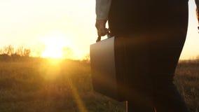 La mujer de negocios en pantalones con la cartera a disposición camina a través de campo en rayos de una puesta del sol hermosa V almacen de metraje de vídeo