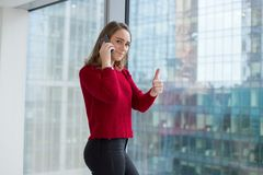 La mujer de negocios en la ventana muestra un finger y habla en el teléfono negociaciones del teléfono y aprobación del resultado foto de archivo libre de regalías