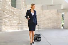 La mujer de negocios en viaje de negocios que camina con el bolso de la rueda y habla fotografía de archivo