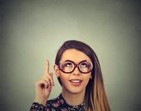 La mujer de negocios en vidrios que señala con el finger para arriba tiene una sonrisa de la idea Imagen de archivo