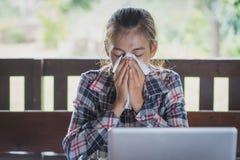 La mujer de negocios enferma con el estornudo en el tejido, mujeres está estornudando imagenes de archivo