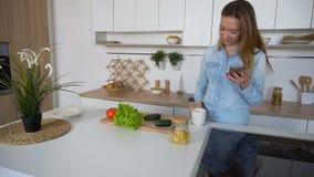 La mujer de negocios entra en la cocina con el teléfono en las manos y el sorbo de las tomas de té, colocándose en el centro de l metrajes