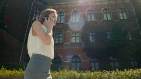La mujer de negocios está hablando por el teléfono mientras que edificio hermoso cercano al aire libre que camina almacen de video