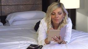 La mujer de negocios está mintiendo en el sofá y está escribiendo en un cuaderno almacen de metraje de vídeo