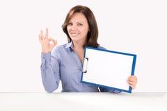 La mujer de negocios está sosteniendo un tablero en blanco Fotos de archivo libres de regalías