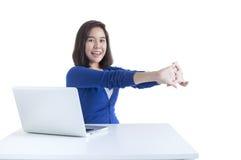 La mujer de negocios estira con el ordenador portátil en frente Foto de archivo