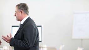 La mujer de negocios felicita al hombre en oficina almacen de video