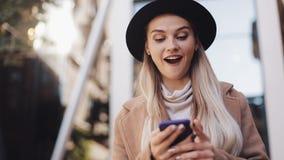 La mujer de negocios feliz en capa con el sombrero que camina cerca de centro de negocio en la ciudad, comunica vía la tableta de almacen de video