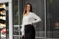La mujer de negocios feliz en uniforme blanco y negro sonríe al aire libre imágenes de archivo libres de regalías