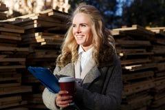 La mujer de negocios feliz que trabaja al aire libre, escribe resultados y café el sostenerse Fotografía de archivo libre de regalías