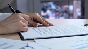 La mujer de negocios firma un acuerdo La mujer firma un documento Firma del contrato de arriendo - firma falsa metrajes